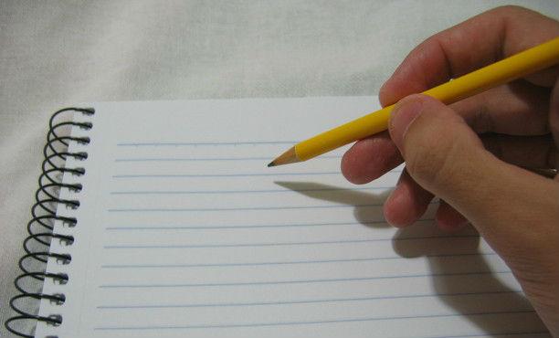 escrevendo a lápis no caderno