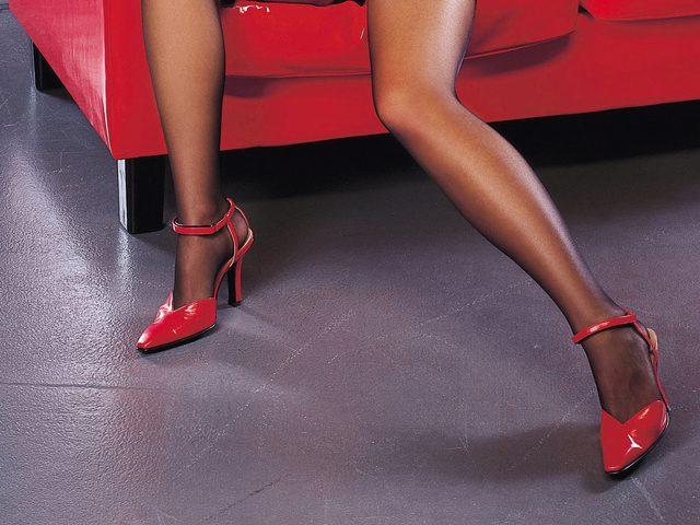 Pernas femininas de meia calça e salto alto