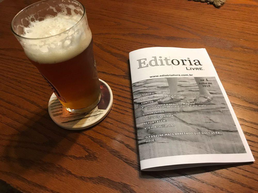 Exemplar impresso do fanzine Editoria Livre ao lado de um copo de cerveja