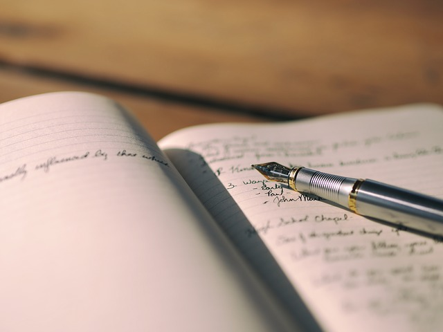 Caneta tinteiro em cima de caderno aberto com anotações