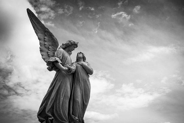 Estátua de anjo levando uma moça pelas mãos