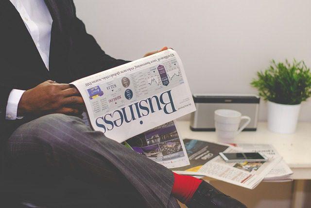 Homem negro, de terno, aparentando ser um empresário, lendo o jornal