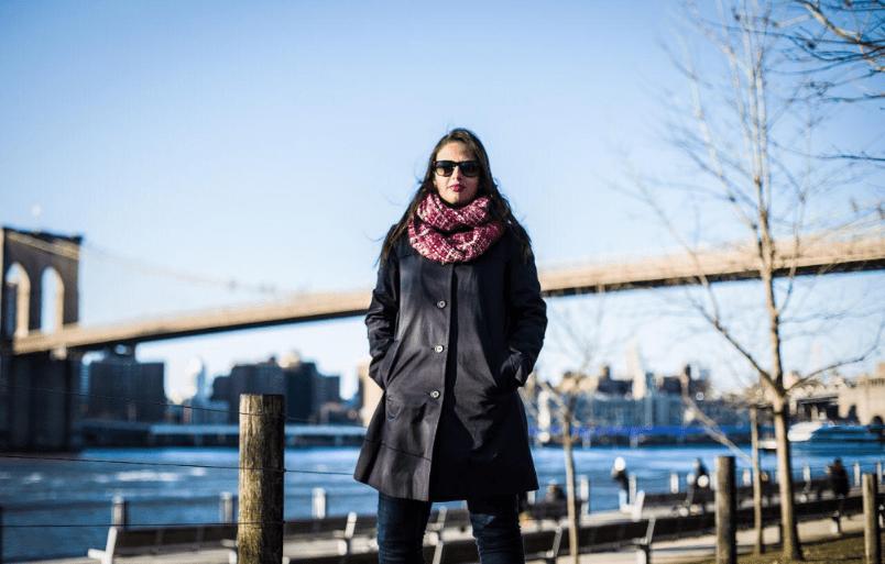 Milena com seu casaco em frente a um rio