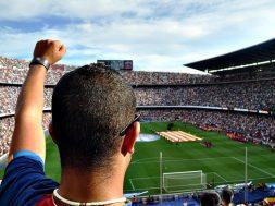 Homem em pé no meio da torcida de um estádio de futebol