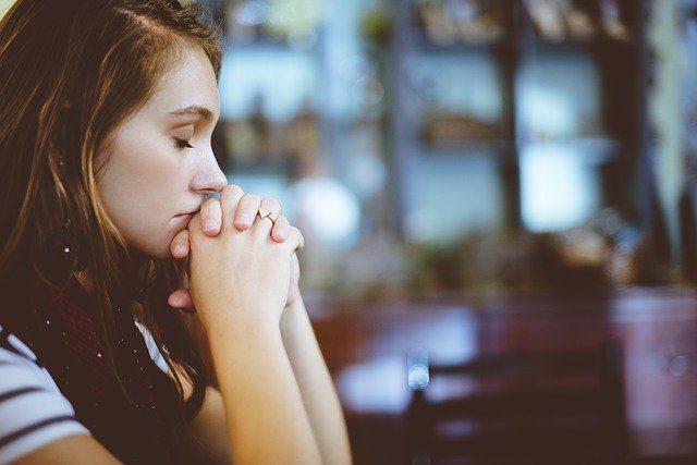 Mulher jovem com os dedos entrelaçados, a mão perto da boca, em posição de oração