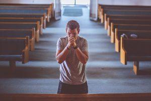 Homem rezando dentro da igreja